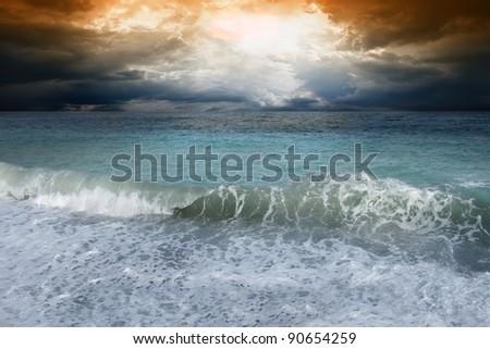 Blue sea, dark sky, sun shines through clouds - stock photo