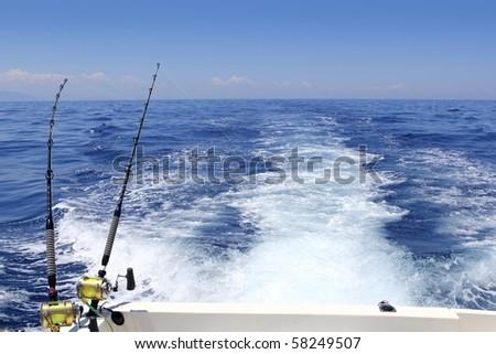 blue sea fishing sunny day trolling rod reels wake ocean big game - stock photo