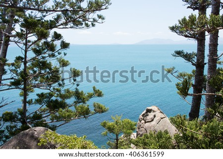 Blue sea framed by Norfolk Island Pines on tropical Magnetic Island, Australia - stock photo