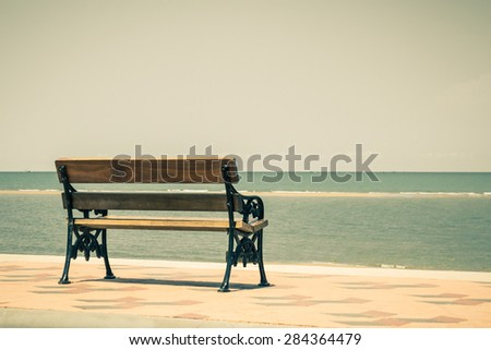 Blue sea,long wood chairs at the tropical beach on blue sky. Concept for rest, relaxation, holidays, spa, resort, Vintage style. - stock photo