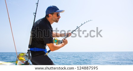 blue sea offshore fishing boat with fisherman holding rod in action - stock photo
