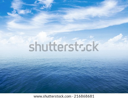 blue sea or ocean water surface with horizon and sky with clouds