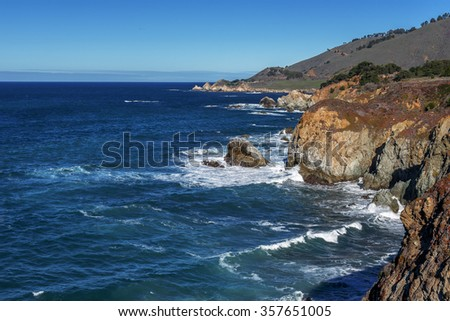 Blue sea & sky, white clouds, waves splashing on huge rocks, off shore, along a rocky coastline, cloud covered mountain tops, traveling the Big Sur Highway (Highway 1) on the California Central Coast. - stock photo