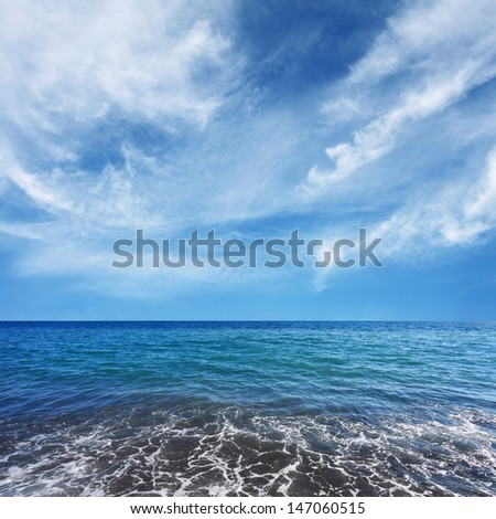 blue sea water and beautiful white clouds on the sky - stock photo