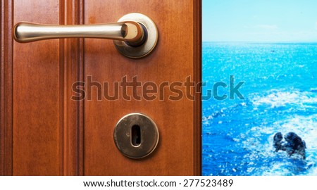 Blue sea with rocks beyond a wooden door, horizontal image - stock photo