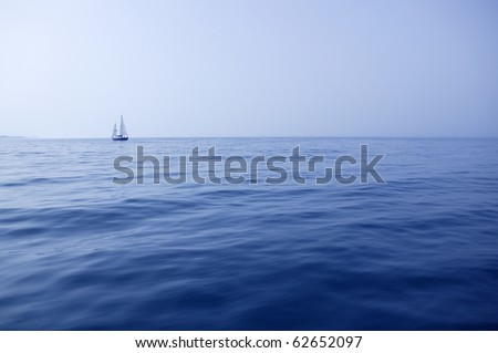 Blue sea with sailboat sailing the ocean surface summer vacation - stock photo