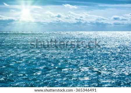 Blue sea with sky, sun rays and clouds. Water natural background