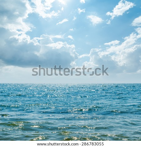 blue sea with sun in clouds - stock photo