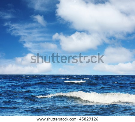 Blue sea with waves and fluffy clouds on blue sky - stock photo