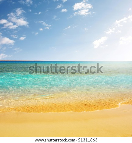 Blue sea yellow sand and blue sky with clouds