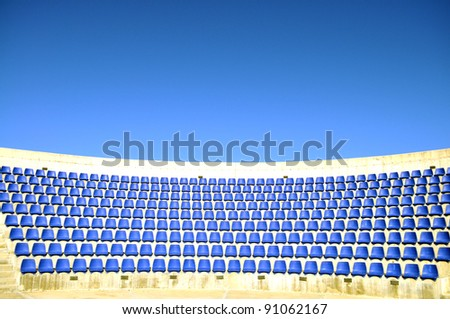 Blue seats and bright sky in an open air stadium - stock photo