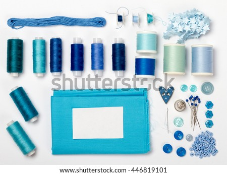 Blue sewing tools and accessories on white fabric