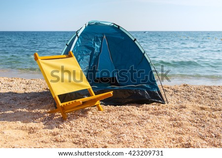 Blue shelter and yellow chair at the beach - stock photo