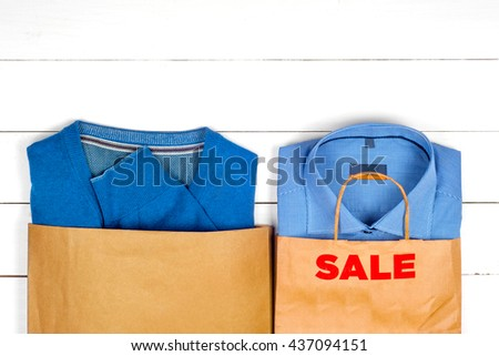 blue shirt and sweater for men  with bags in the sales on wooden white background.  Copy space for text. - stock photo