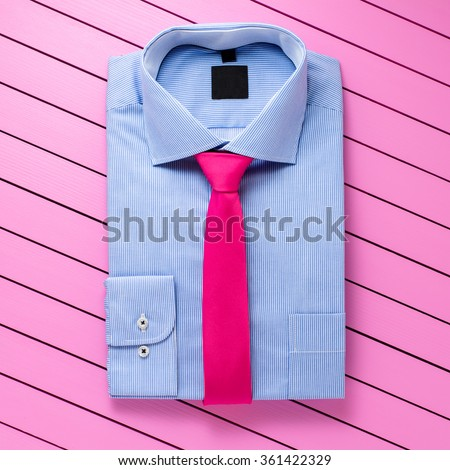 Blue shirt on pink wooden background - stock photo