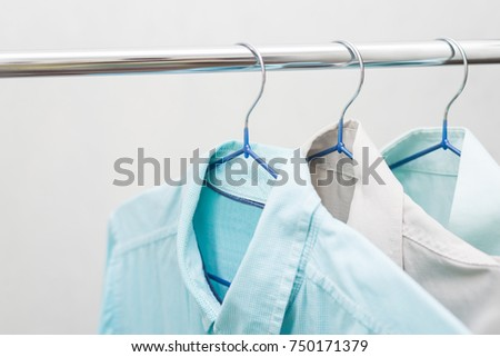 Blue shirts on hangers hanging on a pipe