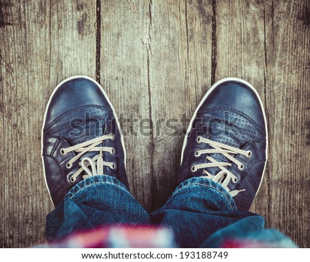 blue shoes on wooden planked floor from above - stock photo
