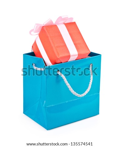 Blue shopping bag with gift on white background.
