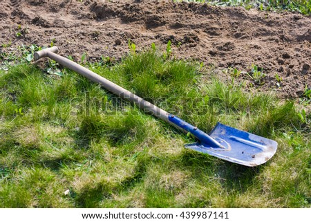 Blue shovel on a green grass