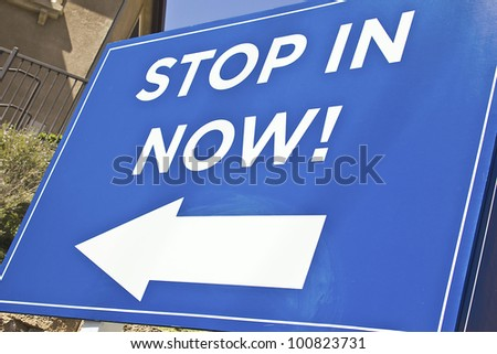 Blue Sign with an arrow reading stop in now. - stock photo