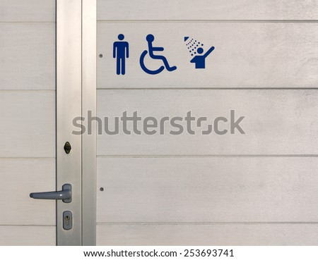 Blue Signs over the Exterior Wall of a Beach Gents Public Bathroom - stock photo