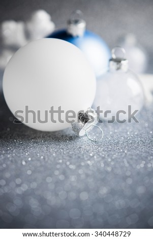 Blue, silver and white xmas ornaments on glitter holiday background. Merry christmas card. Winter holidays. Xmas theme. Happy New Year. - stock photo