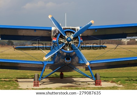 Blue single-engine biplane in retro style. Old airplane. Frontal view of the propeller engine and cockpit. - stock photo