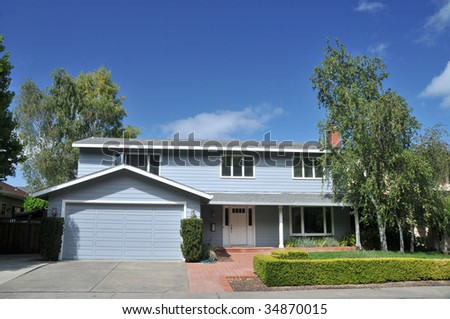 Blue single family house with trees and shrubs in front - stock photo