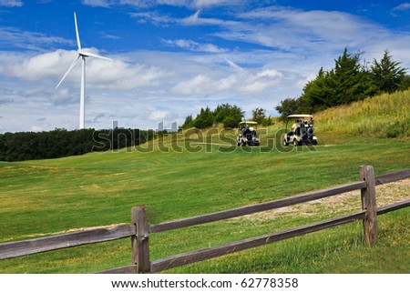 Blue skies, green grass, golf carts and wind generators - stock photo