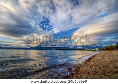 Blue skies on a sandy riverside with distant cityscape - stock photo