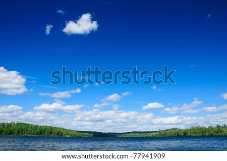 Blue skies over Basswood Lake in the Quetico Wilderness in Canada - stock photo