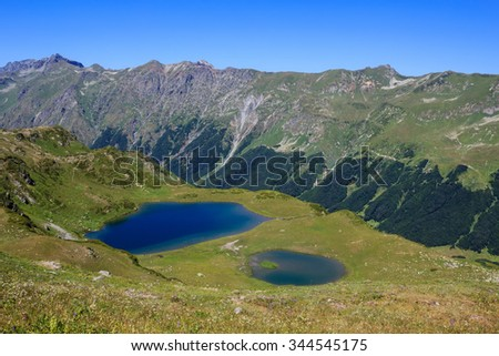 blue sky and blue water of the two mountain lakes surrounded with green alpine meadows and high rocky mountains with forest The Main Caucasian Ridge Abkhazia Georgia - stock photo