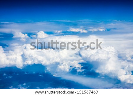 blue sky and clouds from airplane window - stock photo
