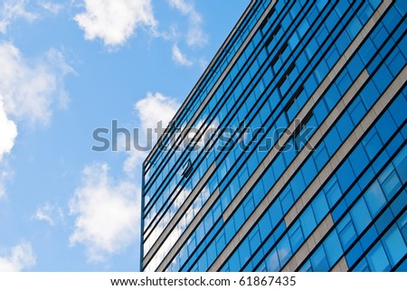 blue sky and clouds reflecting in the glass of an office building - stock photo