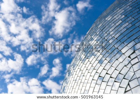 Blue sky and clouds reflecting on a building with mirrored glass.
