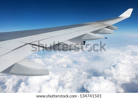 Blue sky and clouds viewing from airplane wing - stock photo