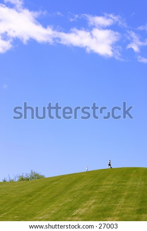 Blue sky and green hill with two small figures - stock photo