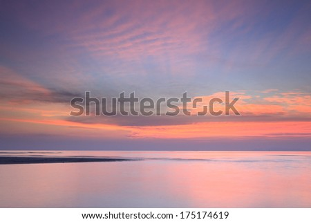 Blue sky and red cloud seascape at dawn  - stock photo