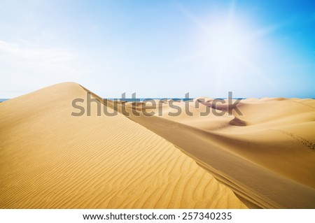 Blue sky and sand dunes. Canary islands, Maspalomas.  The sea on the horizon. - stock photo