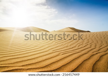 Blue sky and sand dunes with footprints. Canary islands, Maspalomas. Sunset - stock photo