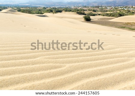 Blue sky and sand dunes with footprints. Canary islands, Maspalomas. The mountains in the background. - stock photo