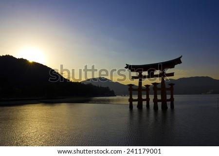 Blue sky and shiny sun on a sunset in Miyajima, with its famous shrine silhouette on the Sea. Hiroshima, Japan. - stock photo