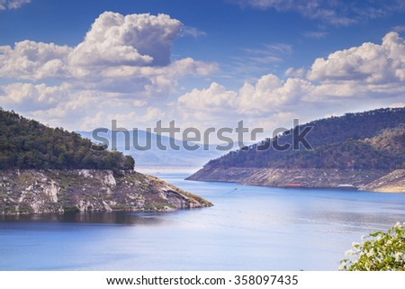 Blue sky and white clouds and a lake In the valley over the Bhumibol Dam in Thailand.