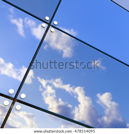 blue sky and white clouds reflect in glass panes of modern building