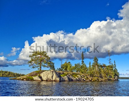 blue sky and  white clouds, rocky island illuminate sun rays