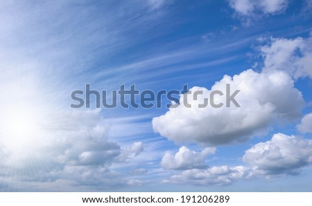 Blue sky background with bright sun and white clouds - stock photo