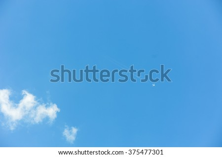 Blue sky background with white clouds and a flying airplane. Blue clear sky panorama with cloud closeup. - stock photo