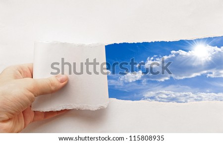 blue sky behind torn paper - stock photo