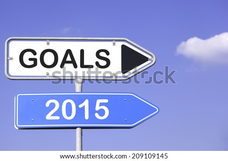 blue sky behind two white and blue road signs  on a metal mast with arrows to the right hand side showing the way to goals 2015 - stock photo