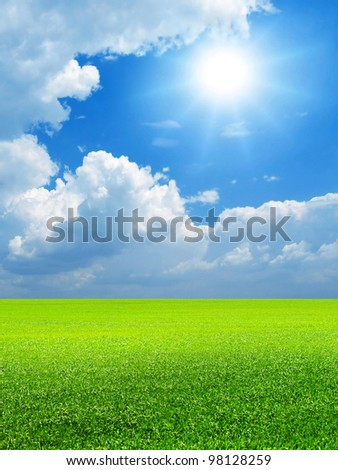 Blue sky, bright sun and green field. - stock photo